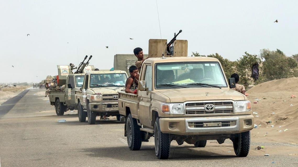 """Yemeni fighters from the Amalqa (""""Giants"""") Brigades gather with armed pick-up trucks and armored vehicles on the side of a road during the offensive to seize the Red Sea port city of Hodeidah. (AFP)"""