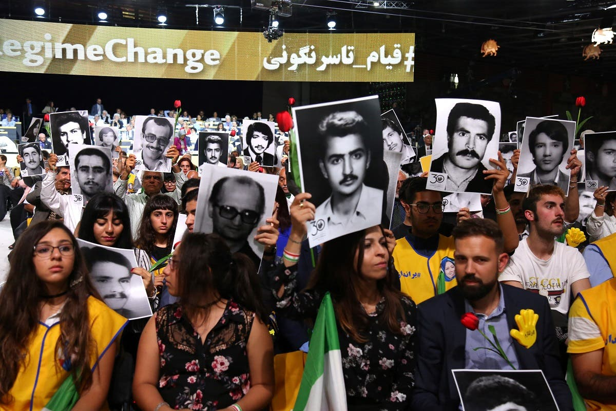 People hold pictures of relatives killed by the Iranian regime, during Free Iran 2018 - the Alternative event on June 30, 2018 in Villepinte. (Reuters)