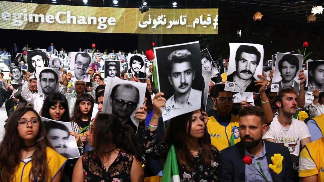 """People hold pictures of relatives killed by the Mohllas regime, during """"Free Iran 2018 - the Alternative"""" event on June 30, 2018 in Villepinte. (Reuters)"""