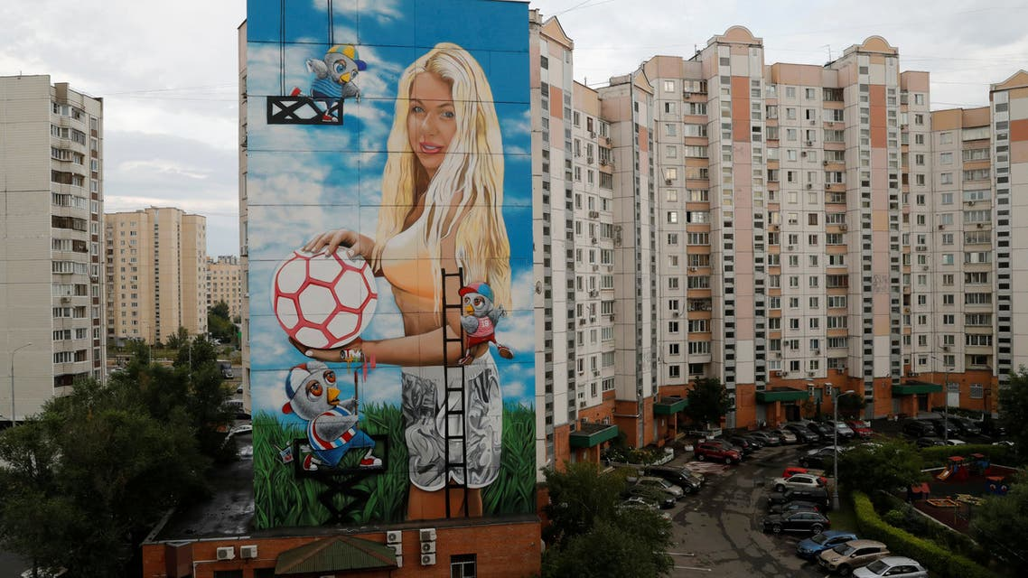 An apartment building decorated with a mural showing Daria Panteleeva, wife of the owner of Novatek Art, a Russian advertising agency whose World Cup themed facades are co-funded by the Russian government, is reflected in a puddle on the outskirts of Moscow, Russia June 30, 2018. Picture taken June 30, 2018. REUTERS/Tatyana Makeyeva NO RESALES. NO ARCHIVES