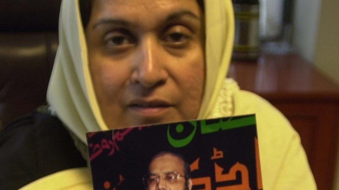 Farhat Paracha, mother of Uzair Paracha, shows her husband's photograph in Karachi, Pakistan, on August 7, 2003. (AP)