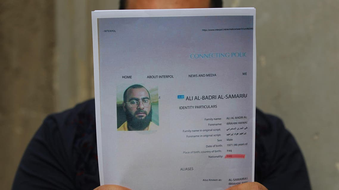 An Iraqi man holds printed profiles of Abu Bakr al-Baghdadi released by Iraqi authorities on February 6, 2018. (AFP)