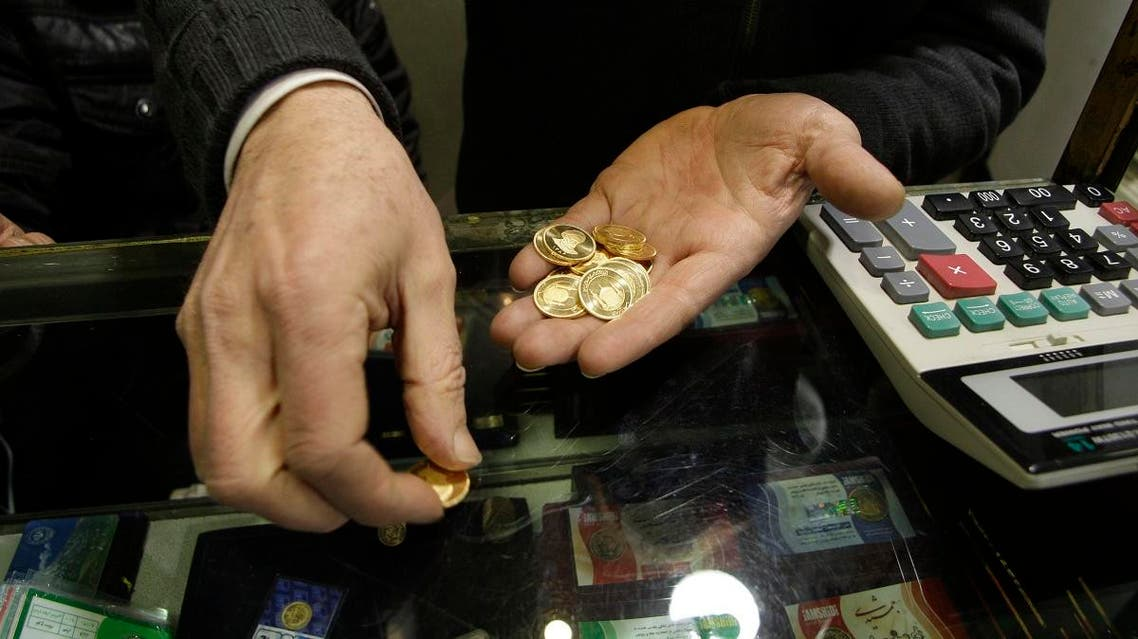 An Iranian goldsmith counts his gold coins at a gold market in the main old Bazaar of Tehran, Iran. (AP)