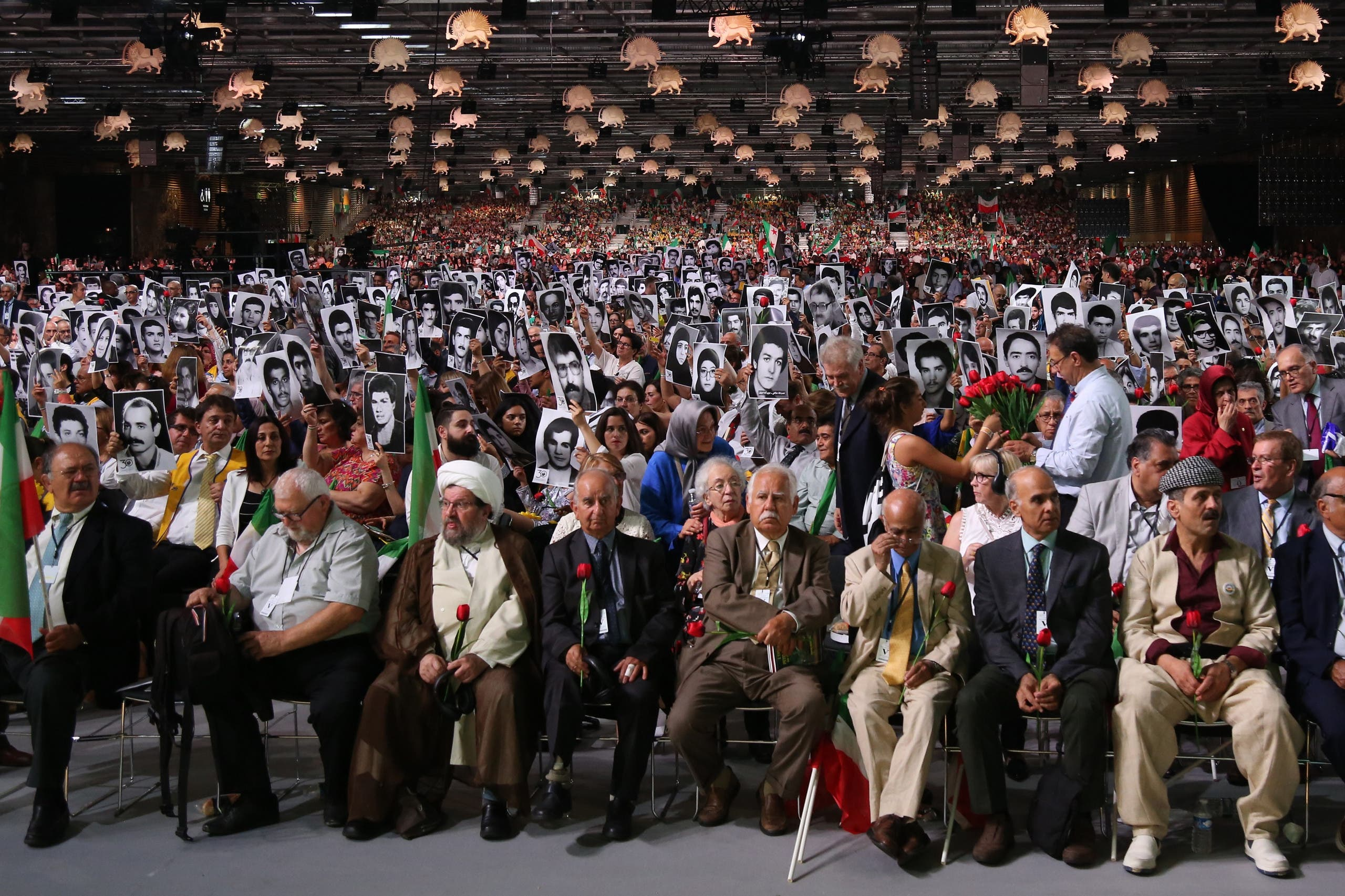 """People hold pictures of relatives killed by Mohllas regime during """"Free Iran 2018"""" event in Villepinte, north of Paris, on June 30, 2018. (AFP)"""