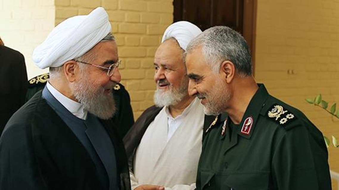A handout picture provided by the office of Iranian President Hassan Rouhani shows him (L) shaking hands with the commander of the Iranian Revolutionary Guard's Quds Force. (AFP)