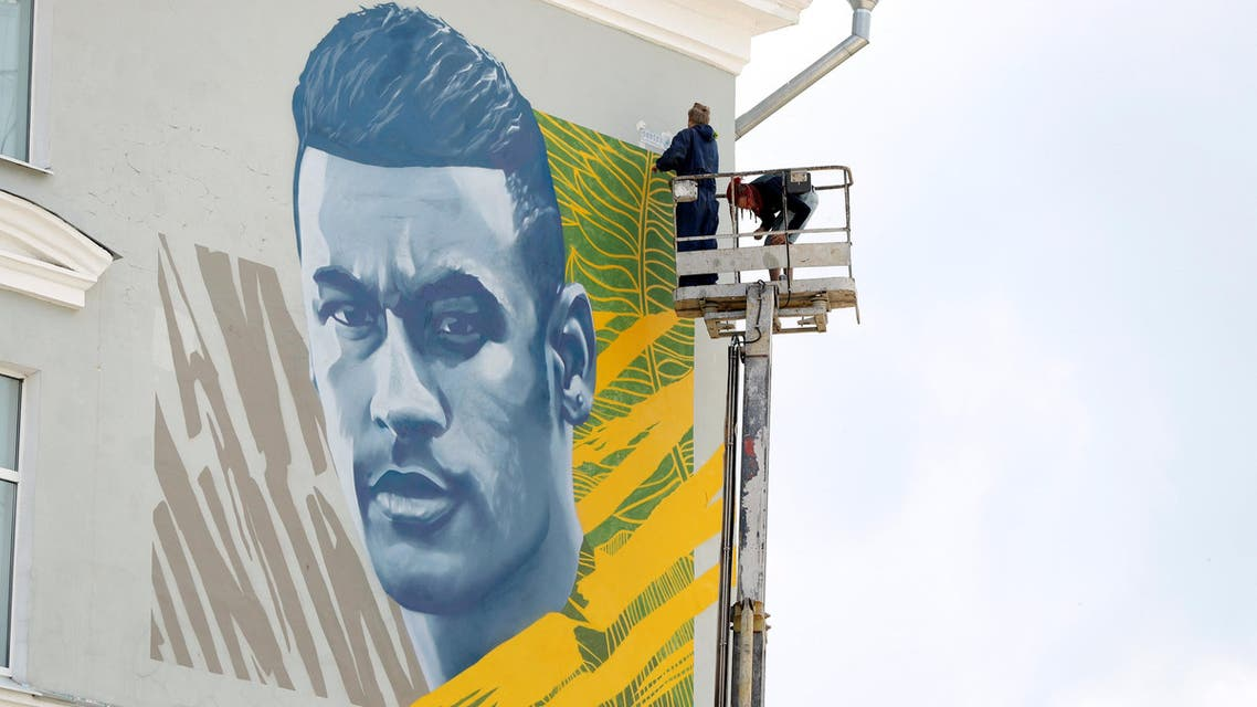 Mural artists painting the face of Neymar on a wall behind the Brazil team hotel. (Reuters)