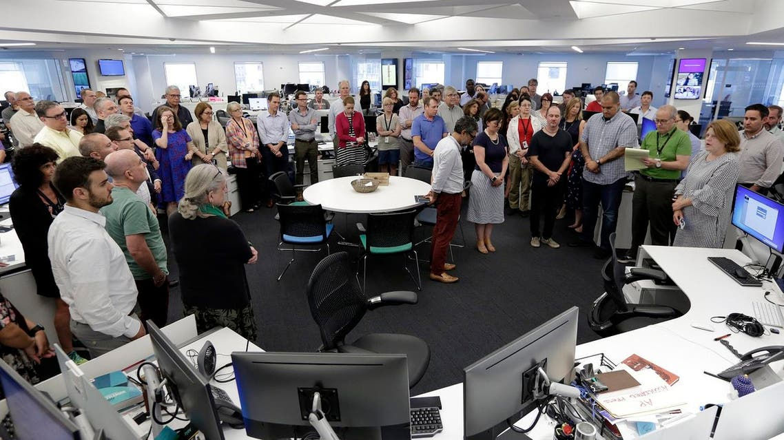 Employees gather in the newsroom of the New York headquarters of The Associated Press, for a moment of silence for the five employees of the Capital Gazettewho were killed a week ago. (AP)