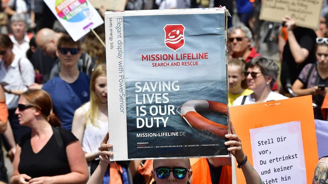 A protester holds a placard during a demonstration to denounce the closure of Mediterranean ports to migrant rescue boats on July 7, 2018 in Berlin. (AFP)