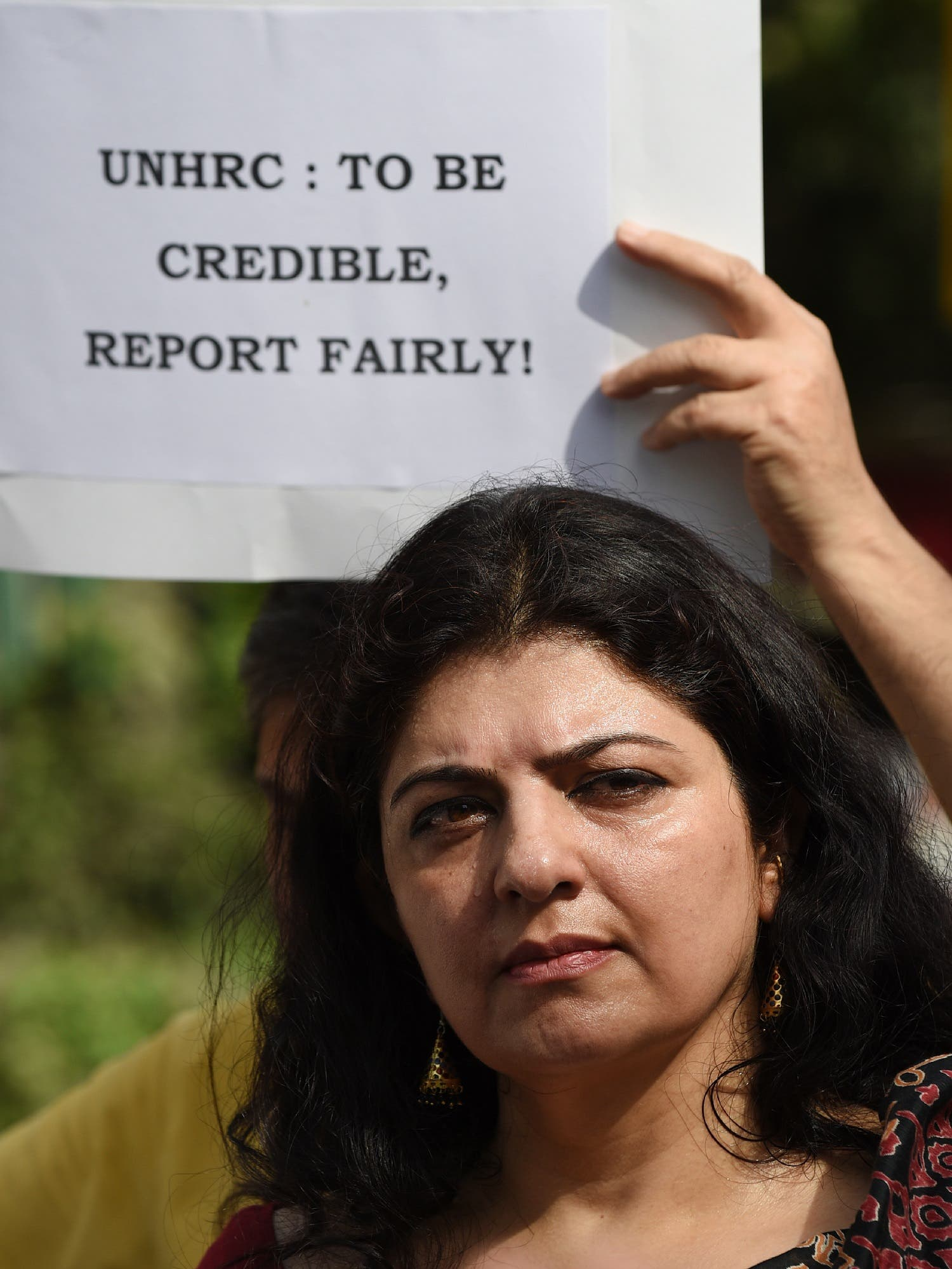 A Kashmiri Hindu protester holds a placard during a protest following the report of Office of the United Nations High Commissioner for Human Rights (OHCHR) outside the UN office in New Delhi on June 25, 2018. (AFP)