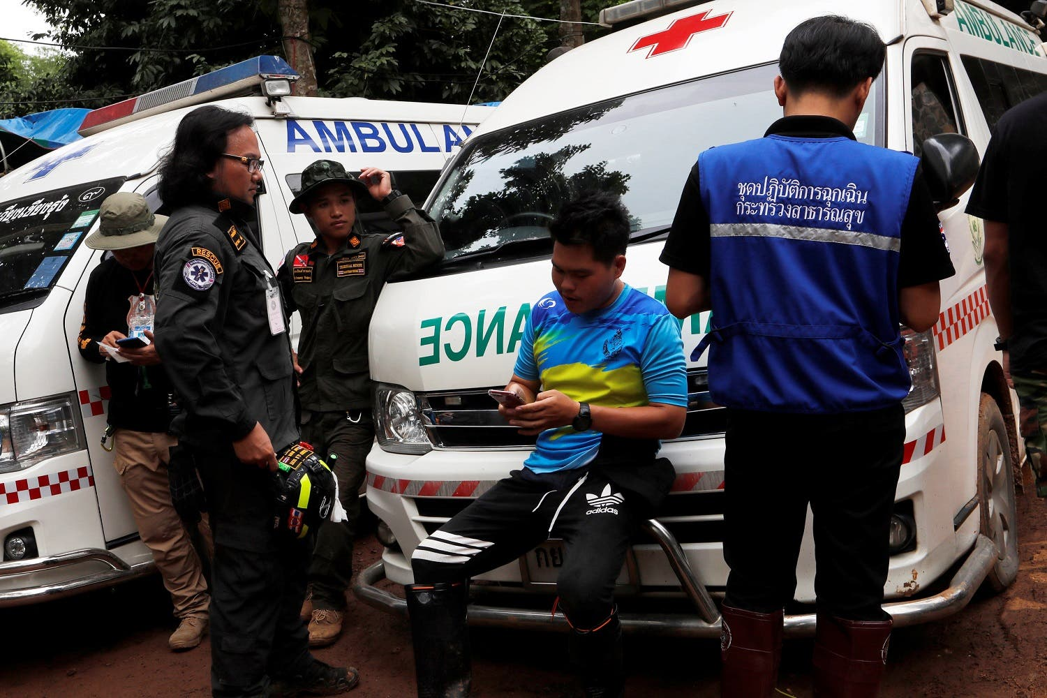 Men standby near ambulances outside Tham Luang cave complex, where 12 schoolboys and their soccer coach are trapped inside a flooded cave, in the northern province of Chiang Rai, Thailand, July 7, 2018. (Reuters)