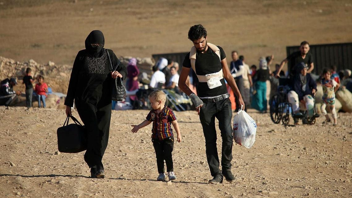 Syrians walk carrying their belongings on August 22, 2017 after crossing the Syria-Jordan border near the town of Nasib as they return to their homes following a US-Russia ceasefire brokered in three southern provinces, Daraa, Quneitra, and Sweida earlier in the year. Mohamad ABAZEED / AFP