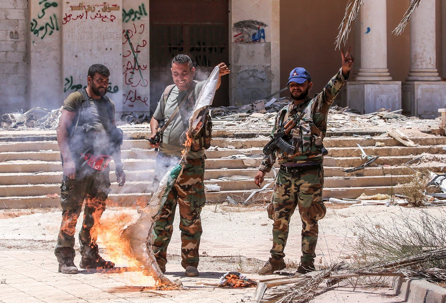 Syrian government soldiers burn an opposition flag while flashing the victory gesture at the Naseeb border crossing with Jordan in the southern province of Daraa on July 7, 2018. (AFP)