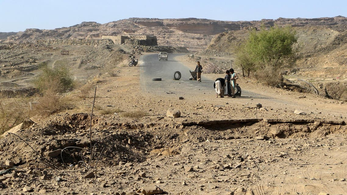 Yemeni men stand next to damaged road following an air strike on the northwestern Huthi-held Saada province on January 24, 2018. (AP)