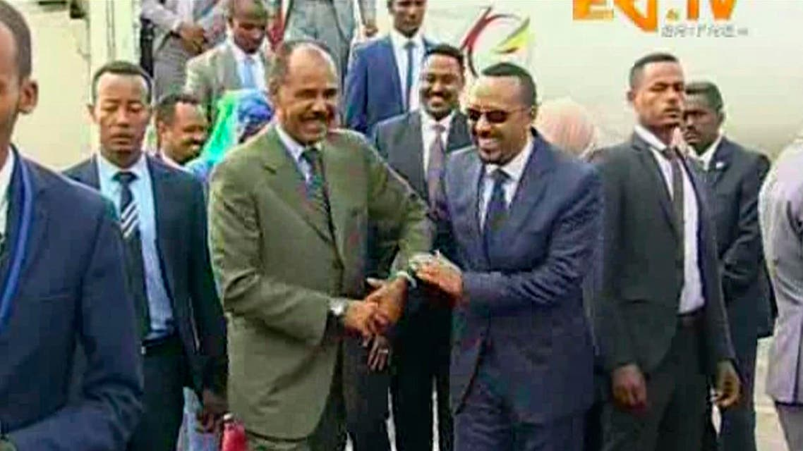 Ethiopia's Prime Minister Abiy Ahmed, centre right is welcomed by Erirea's President Isaias Afwerki as he disembarks the plane, in Asmara, Eritrea. (ERITV via AP)