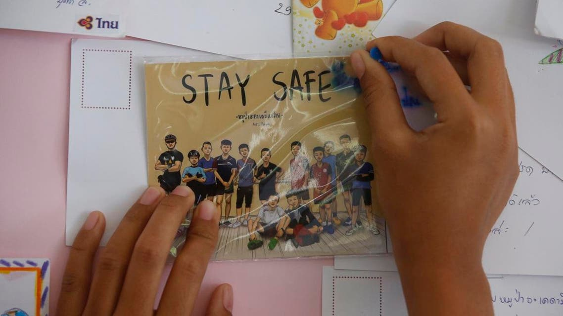 A Thai well wisher puts a poster to pray for boys and their soccer coach who have been trapped since June 23, in Mae Sai, Chiang Rai province. (AP)