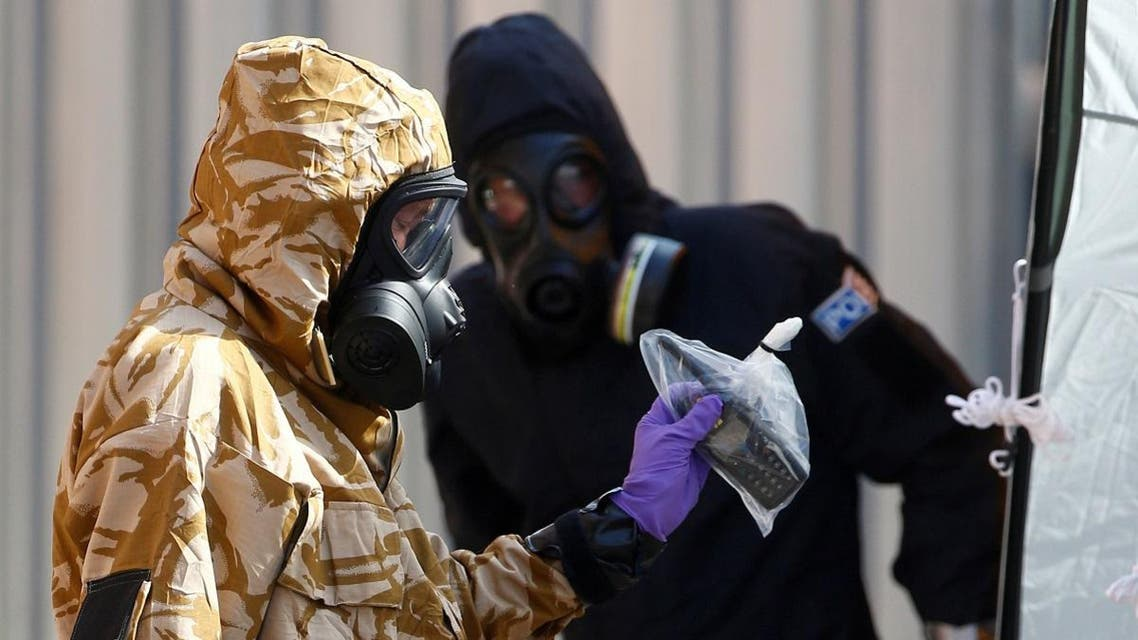 Forensic investigators, wearing protective suits, emerge from the rear of John Baker House, after it was confirmed that two people had been poisoned with the nerve-agent Novichok, in Amesbury. (Reuters)