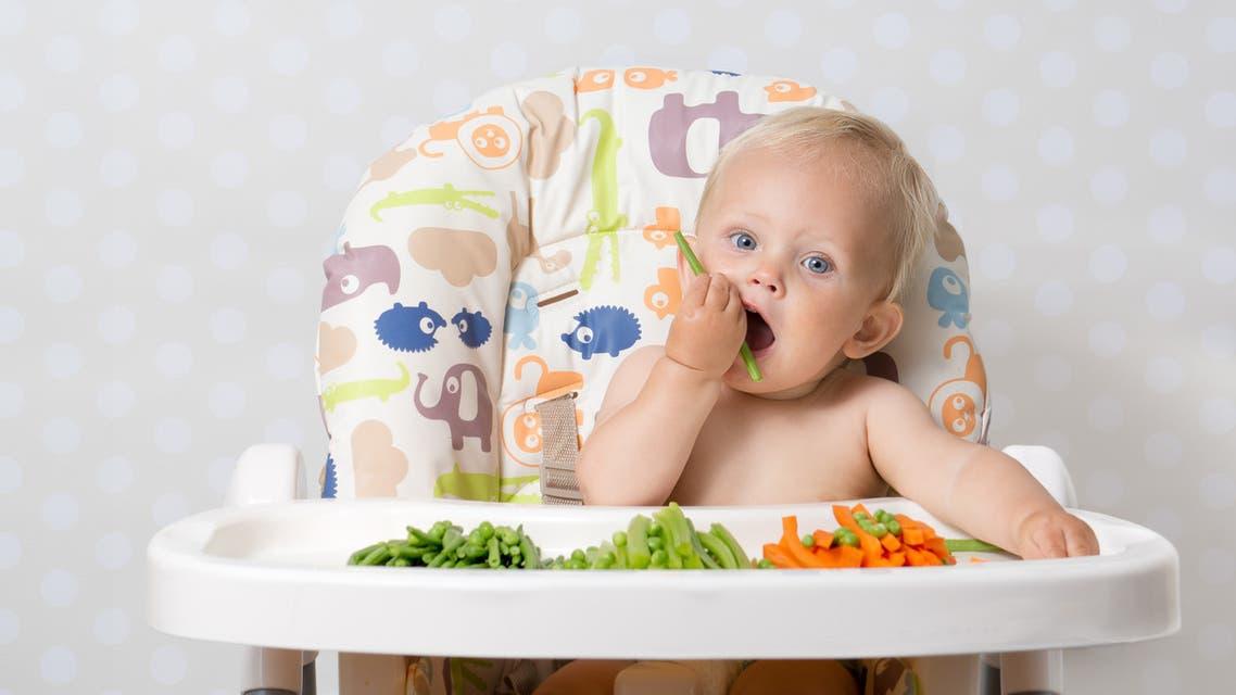 Baby girl eating raw food - Stock image