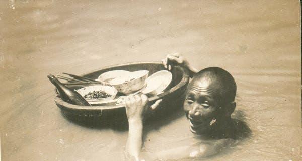 صورة لرجل صيني وهو يحاول إنقاذ بعض ممتلكاته عقب الفيضان