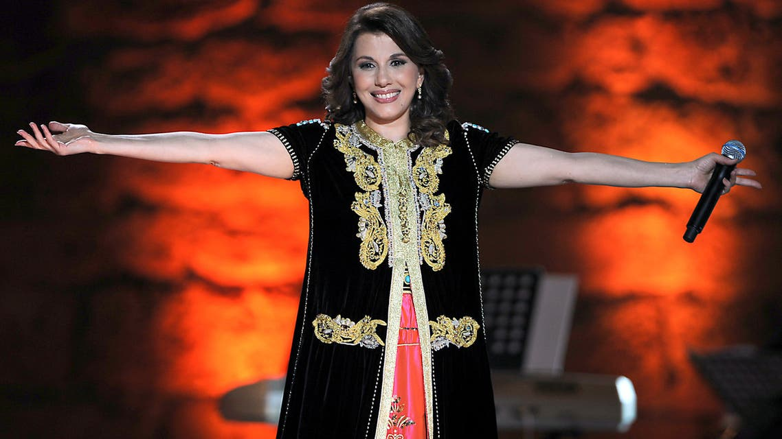 Lebanese singer singer Mejda Al Roumi acknowledges applauds from the audience during the opening of the 46th session of the International Carthage festival at the Roman theatre in Carthage near Tunis late on July 09 2010