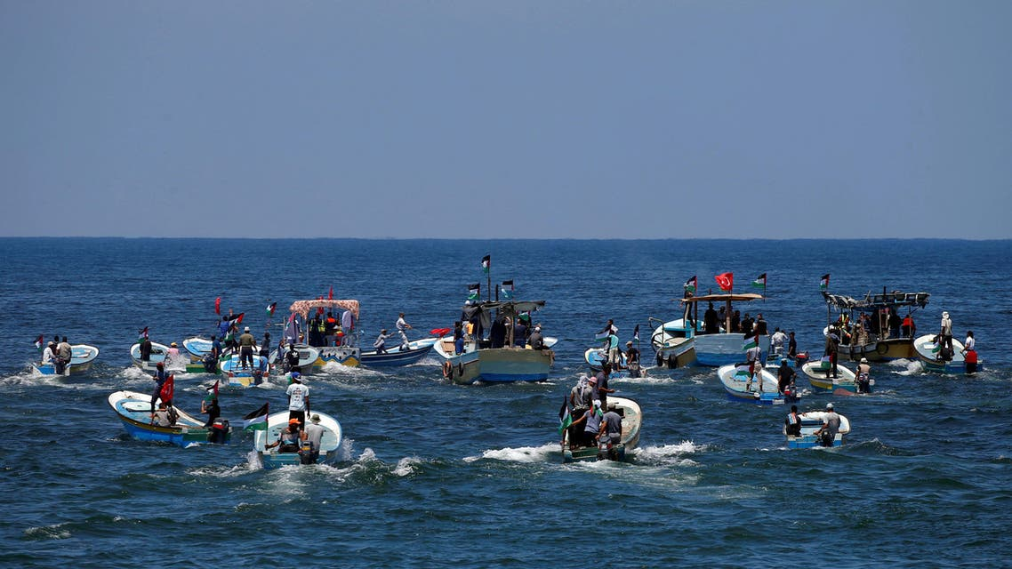 People ride boats as a boat carrying Palestinian patients and students sails towards Europe aiming to break Israel's blockade on Gaza, at the sea in Gaza July 10, 2018. REUTERS