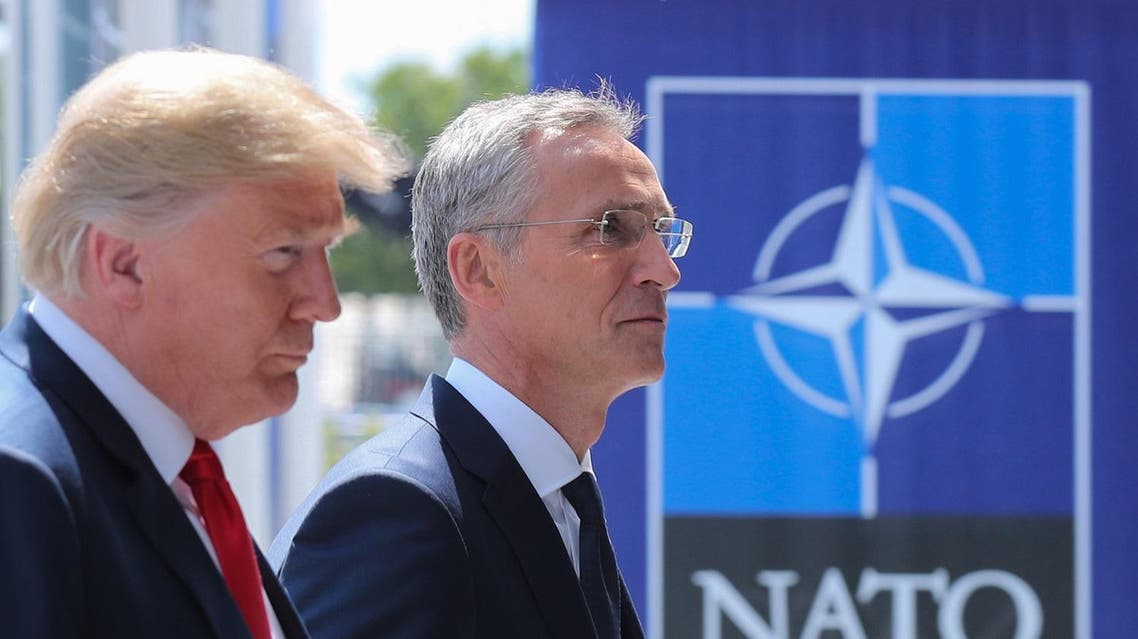 US President Donald Trump (L) walks with NATO Secretary General Jens Stoltenberg as he arrives to attend the NATO summit, in Brussels, on July 11, 2018. (AFP)
