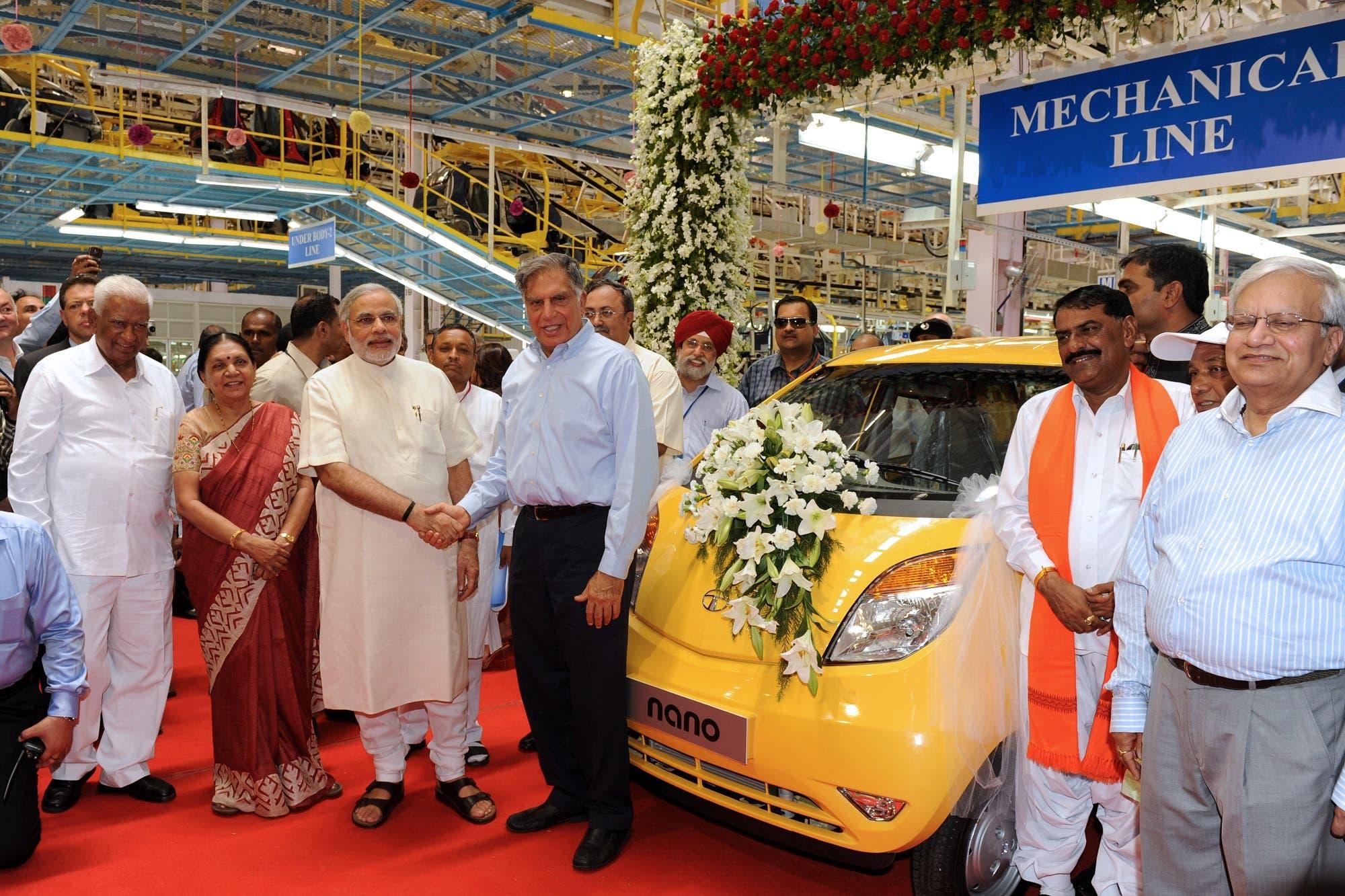 Ratan Tata (C) and then Gujarat Chief Minister Narendra Modi (5th L) pose besides a Nano car at the new Nano plant near Ahmedabad on June 2, 2010. (AFP)