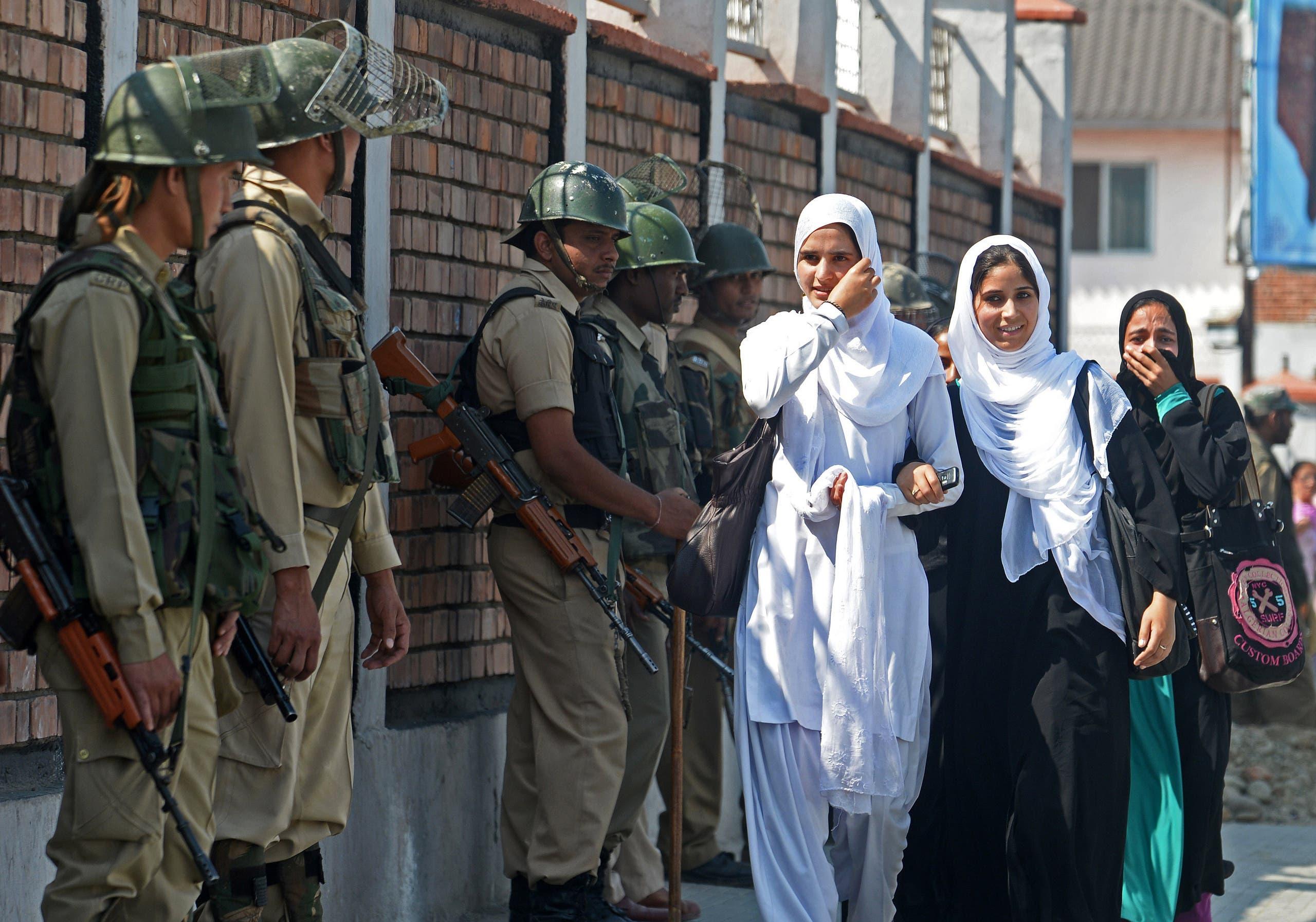 Indian paramilitary troopers stand guard as Kashmiri Muslim school girls walk past in Srinagar on October 1, 2013. (AFP)