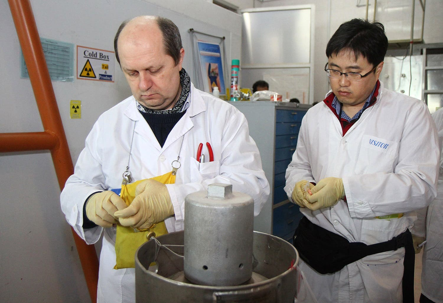 Unidentified IAEA inspectors seal after disconnecting the connections between the twin cascades for 20 percent uranium production at nuclear power plant of Natanz on January, 20, 2014. (AFP)