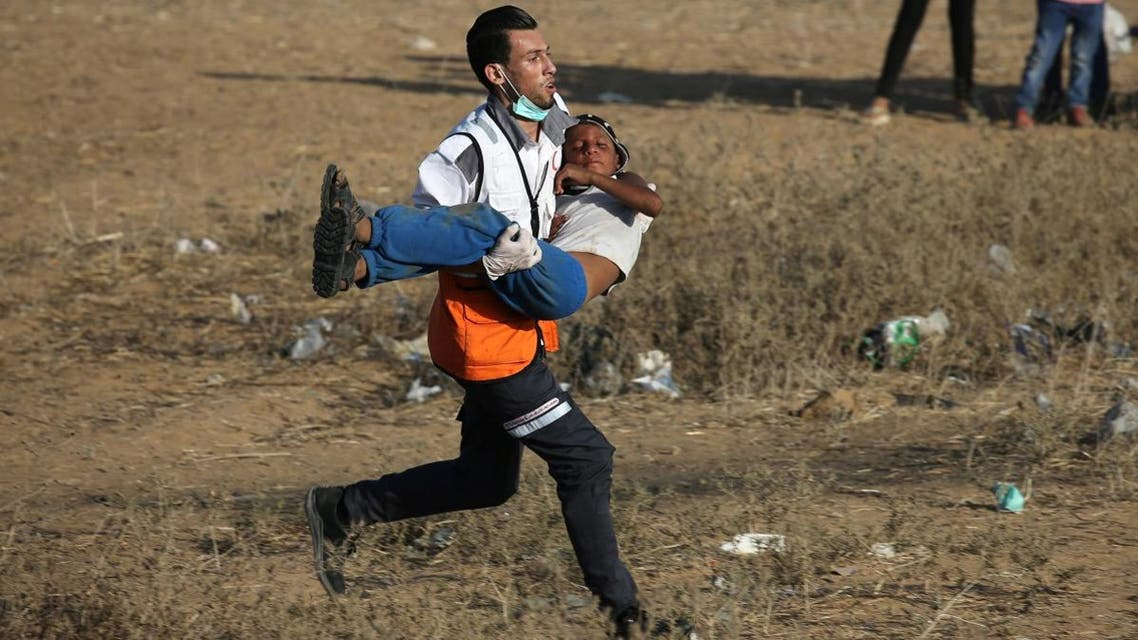A medic evacuates a Palestinian boy after inhaling tear gas fired by Israeli troops during a protest at the Israel-Gaza border in the southern Gaza Strip July 6, 2018. (Reuters)