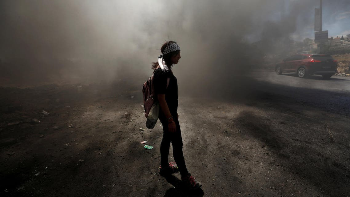 A Palestinian girl stands amongst smoke during clashes with Israeli troops near the Jewish settlement of Beit El, near Ramallah, in the occupied West Bank on June 29, 2018. (Reuters)