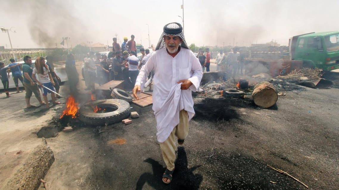 Iraqi protesters burn tires and block the road at the entrance to the city of Basra. (Reuters)