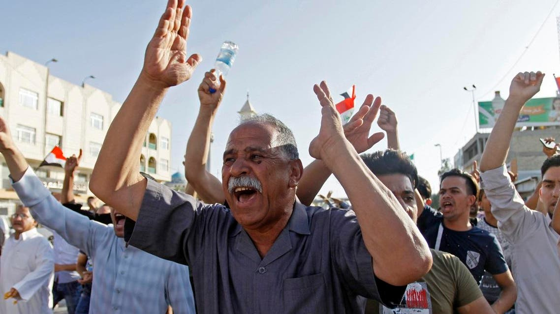 Iraqis shout slogans while gathering during a demonstration in the central shrine city of Najaf on July 13, 2018. (AFP)