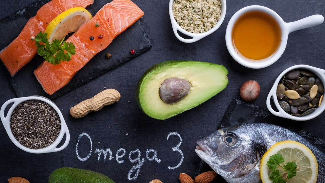 Black slate table with product rich in omega 3 and vitamin D. Written word omega 3 by white chalk. - Stock image