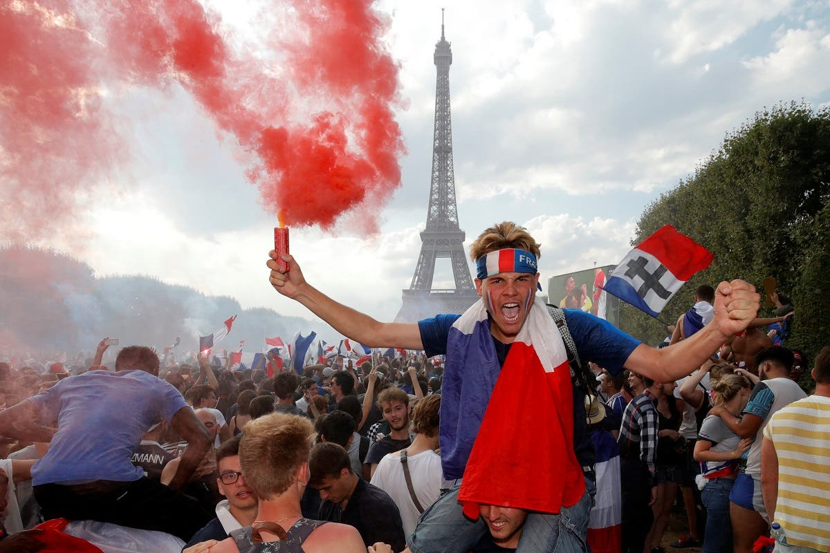 France fan holds a smoke cannister as he celebrates in front of the Eiffel Tower after France win the World Cup. (Reuters)