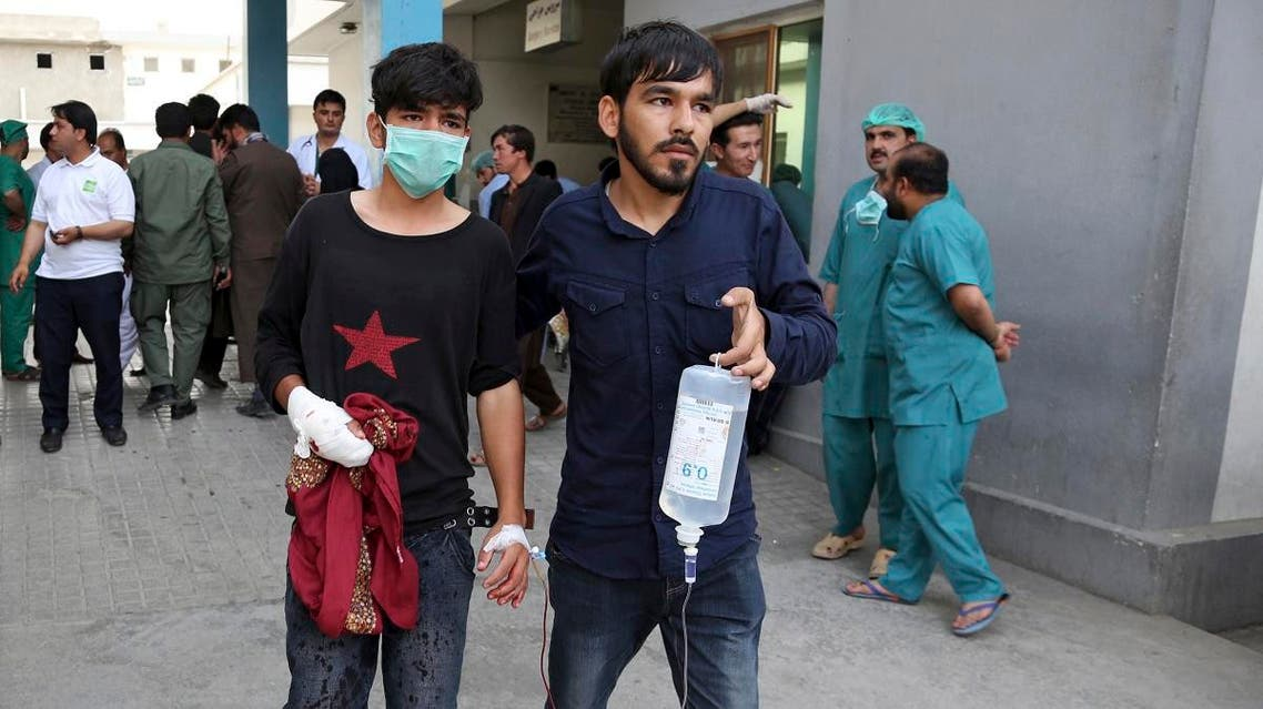 An injured youth is escorted to a hospital following a deadly attack outside the Rural Rehabilitation and Development Ministry in Kabul. (AP)