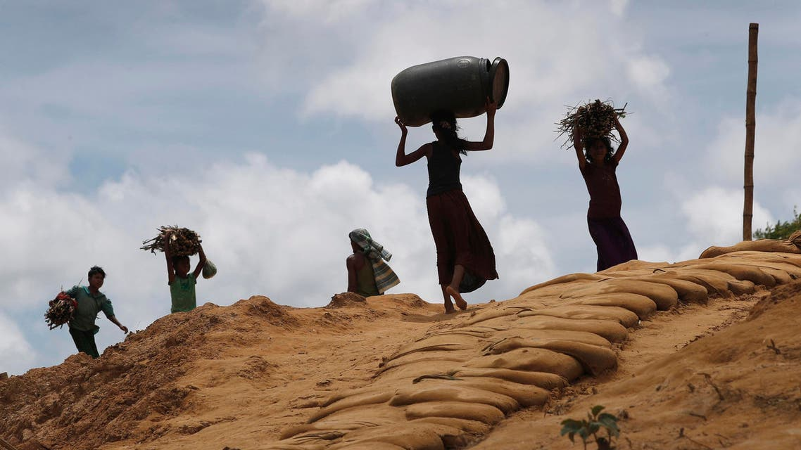 Rohingya girls carry firewood on their heads as they make their way through Kutupalong refugee camp in Bangladesh on June 28, 2018. (AP)