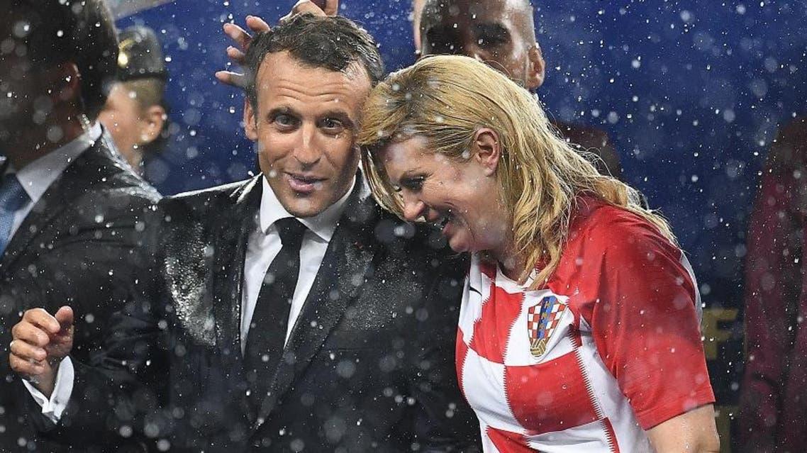 French President Emmanuel Macron (L) talks with Croatian President Kolinda Grabar-Kitarovic during the trophy ceremon