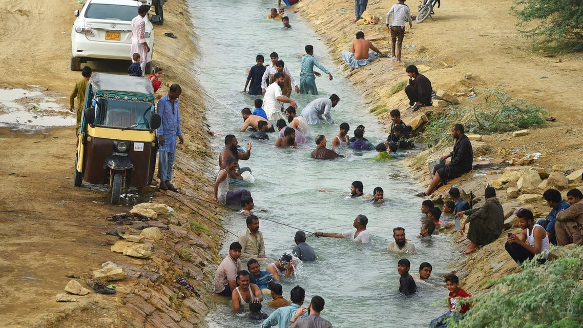 Pakistani residents cool off at a canal during heatwave as temperatures reach 44 degrees celsius in Karachi on May 30, 2018.