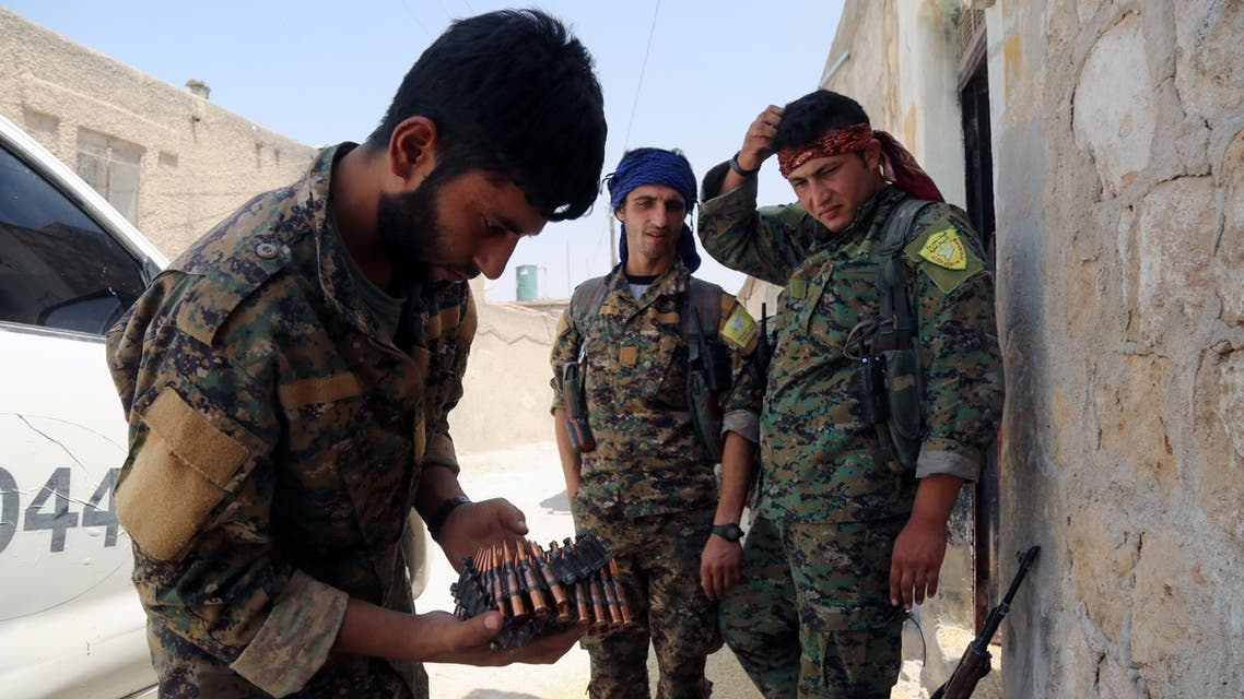 """Members of the Syrian Democratic Forces (SDF), one holding ammunition, stand on a street in the northern Syrian town of Manbij on August 7, 2016, as they comb the city in search of the last remaining jihadists, a day after they retook it from the Islamic State group. A coalition of Arab and Kurd fighters on August 6, 2016 seized the Islamic State (IS) group stronghold of Manbij, two months after launching an operation to capture the strategic city in northern Syria, a monitor said. The town had served as a key transit point along IS's supply route from the Turkish border to Raqa, the de facto capital of its self-styled Islamic """"caliphate""""."""