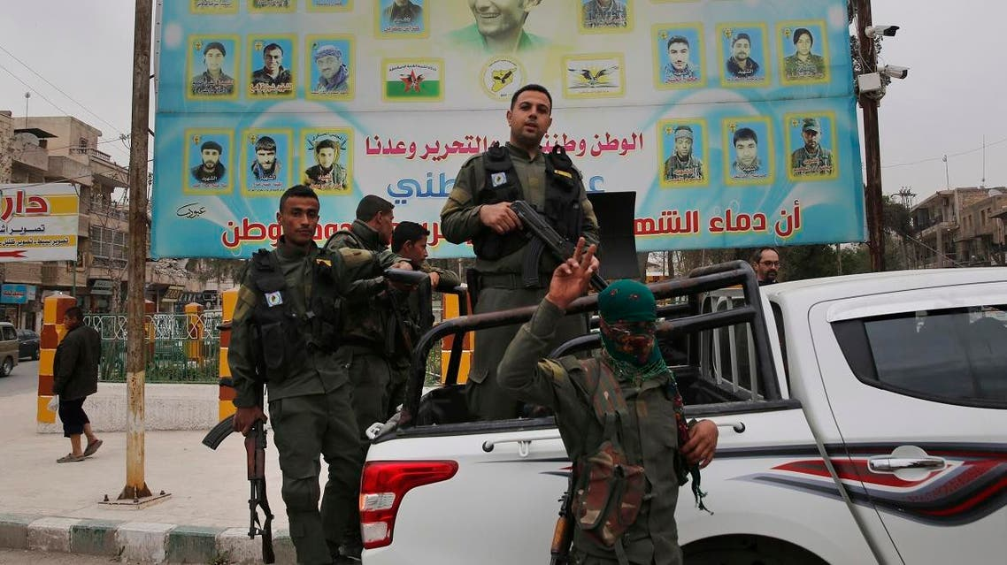 members of the Kurdish internal security forces stand on their vehicle in front of a giant poster showing portraits of fighters killed fighting against the Islamic State group, in Manbij, north Syria. (File photo: AP)