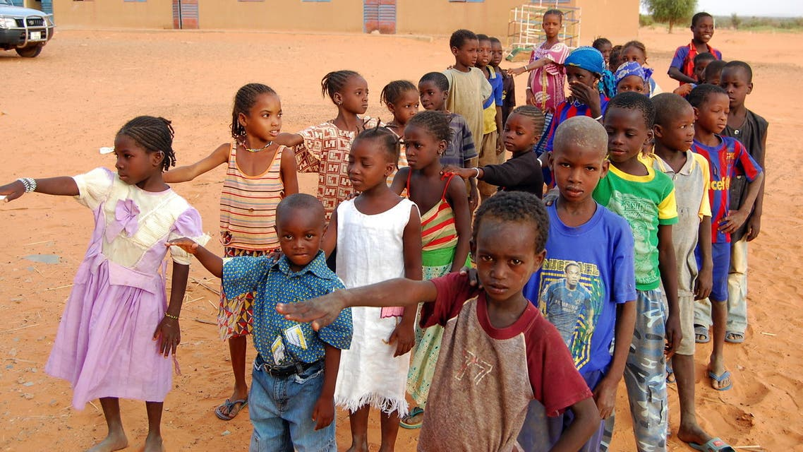 Children get ready to enter a class room in Yakouta on June 10, 2009. In Burkina Faso's arid northern region classes burst at the seams at the start of the school year but as the year progresses more and more parents take their children out of school: the boys leave to herd cattle and many girls get married off early. In the last few years teachers, parents and non-governmental organisations and the local authorities have come up with a number of new ways to fight against early school leaving.