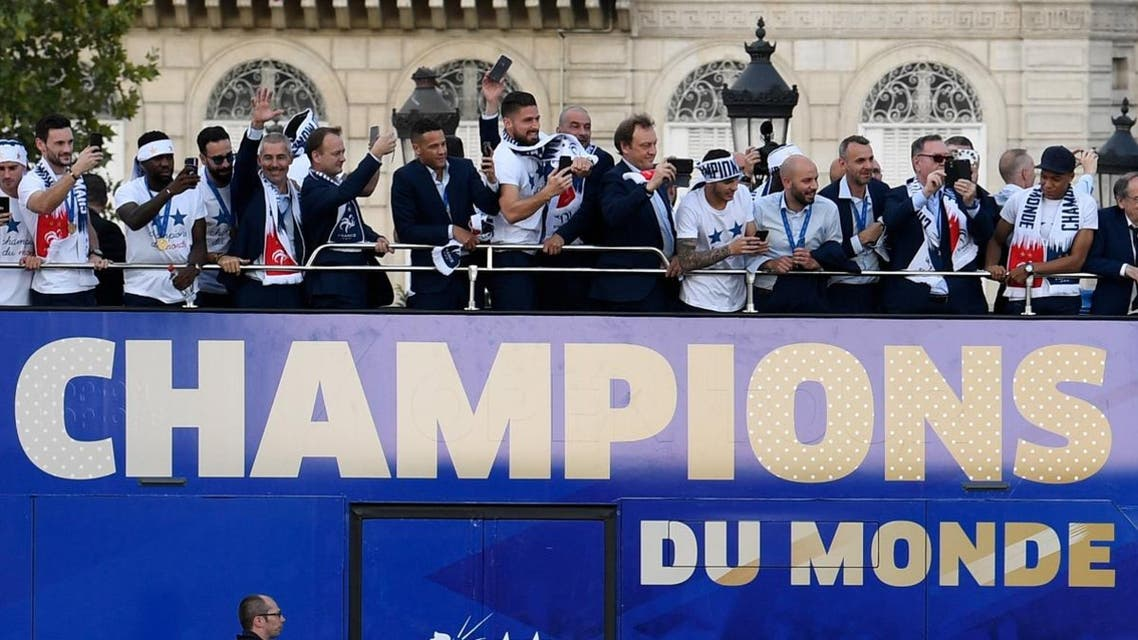 France's national soccer team players take pictures with their mobile phones as they celebrate with teammates on the roof of a bus. (Reuters)