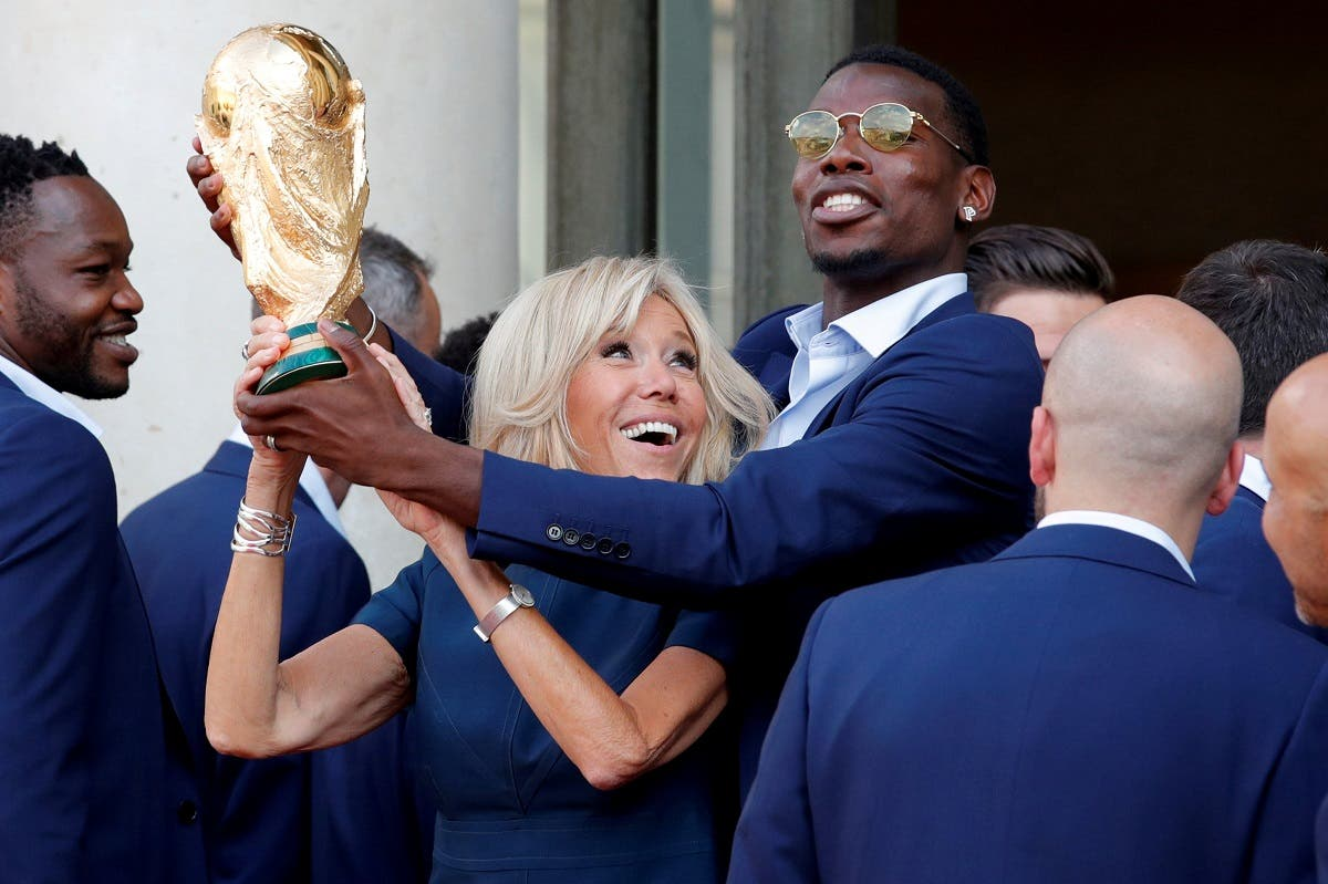 Brigitte Macron, the wife of French President Emmanuel Macron, and player Paul Pogba hold the trophy before a reception to honour the France soccer team after their victory in the 2018 Russia Soccer World Cup, at the Elysee Palace in Paris. (Reuters)