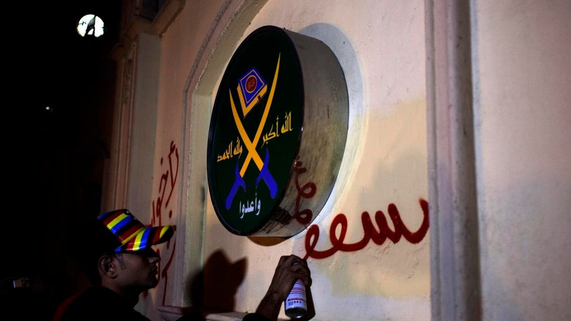 """An Egyptian activist spray paints a slogan in Arabic that reads """"Brotherhood are sheep,"""" next to a logo of the Muslim Brotherhood. (File photo: AP)"""