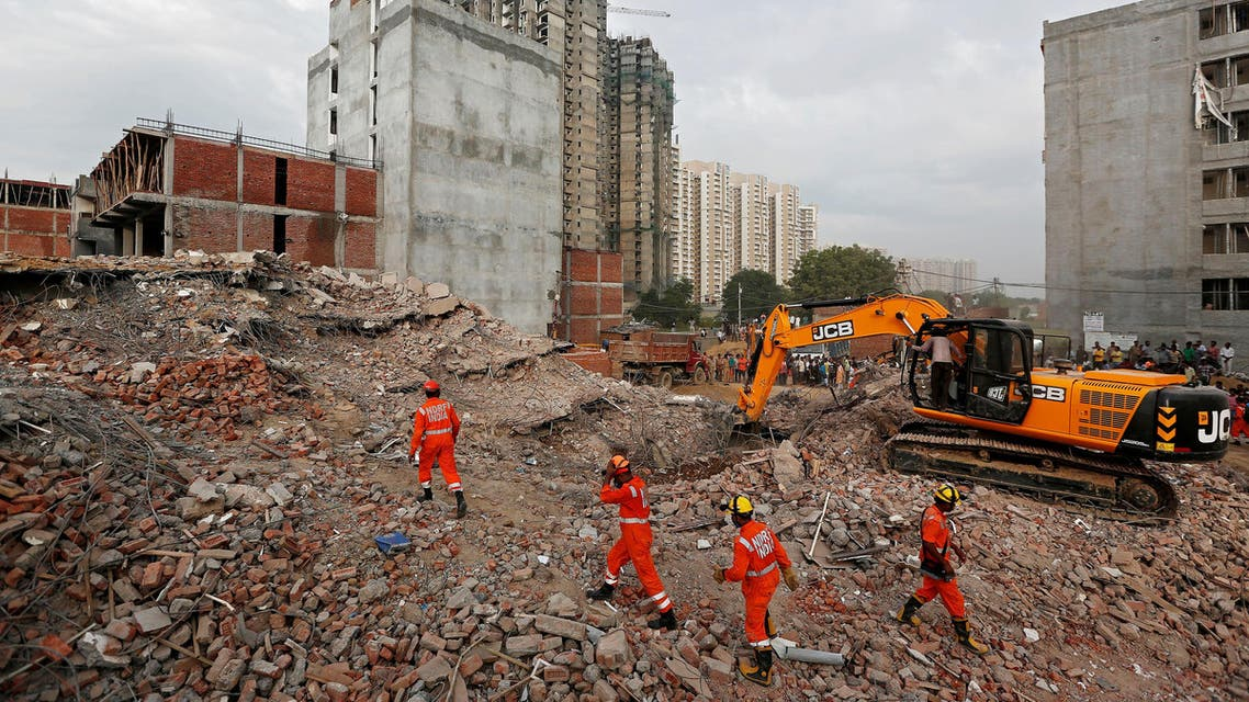 Rescue workers look for survivors among the rubbles at the site of a collapsed building in Greater Noida, on July 19, 2018. (Reuters)