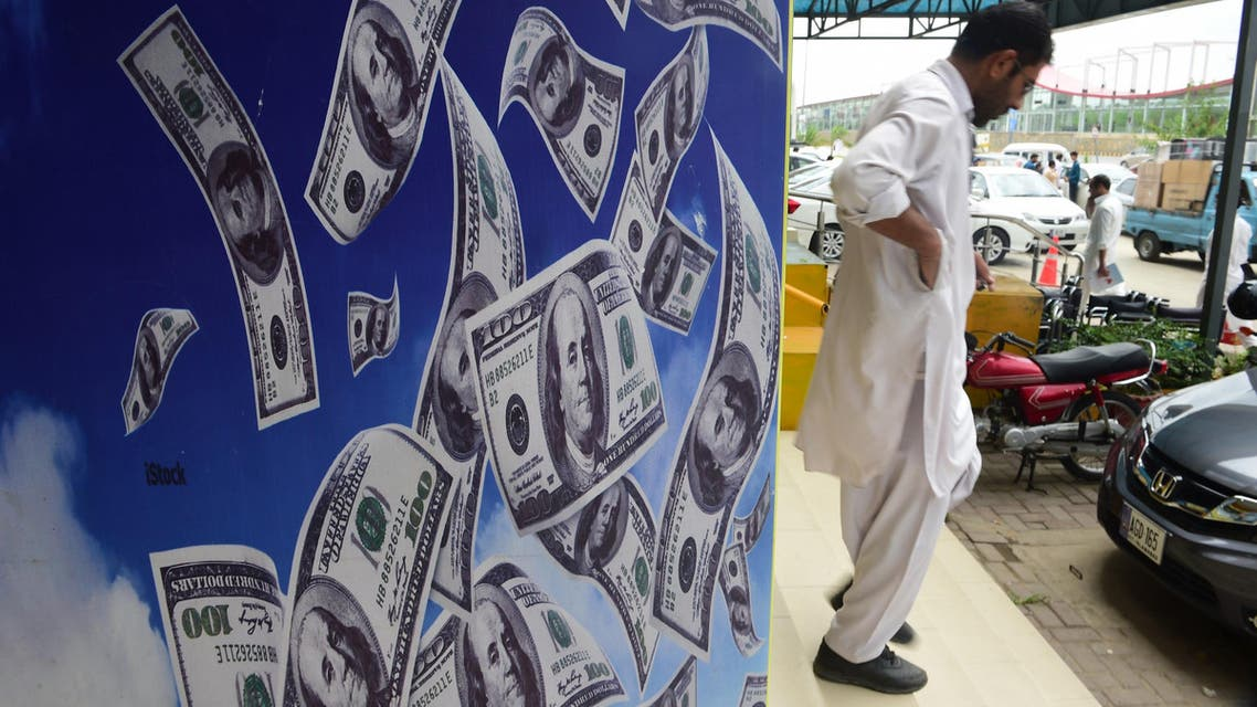 A Pakistani man walks past a currency exchange shop in Islamabad on July 3, 2018. (AFP)