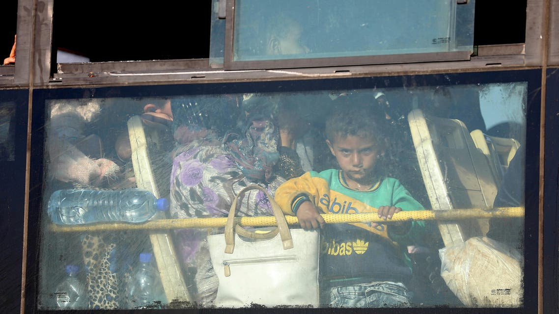 A Syrian child lokks through the windows of a bus as displaced people from the Quneitra province wait at the Murak crossing point to be carried in the provinces of Idlib and Aleppo, in Murak, northwestern Syria, on July 21, 2018. The transfers come under a surrender deal agreed this week between Russia and Syrian rebels in Quneitra province that will see the sensitive zone fall back under state control. Rebels will hand over territory they control in Quneitra and the neighbouring buffer zone with the Israeli-occupied Golan, a war monitor and a rebel source told AFP.