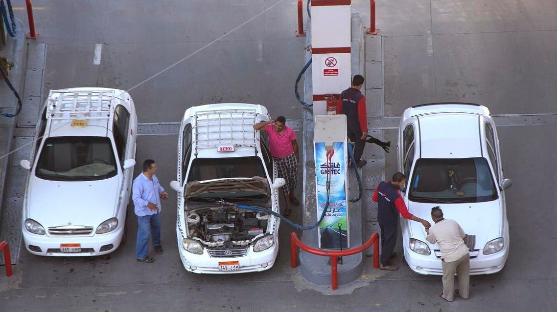 Taxi drivers chat as they refuel their vehicles at a gas station in Cairo on June 29, 2017. (AP)