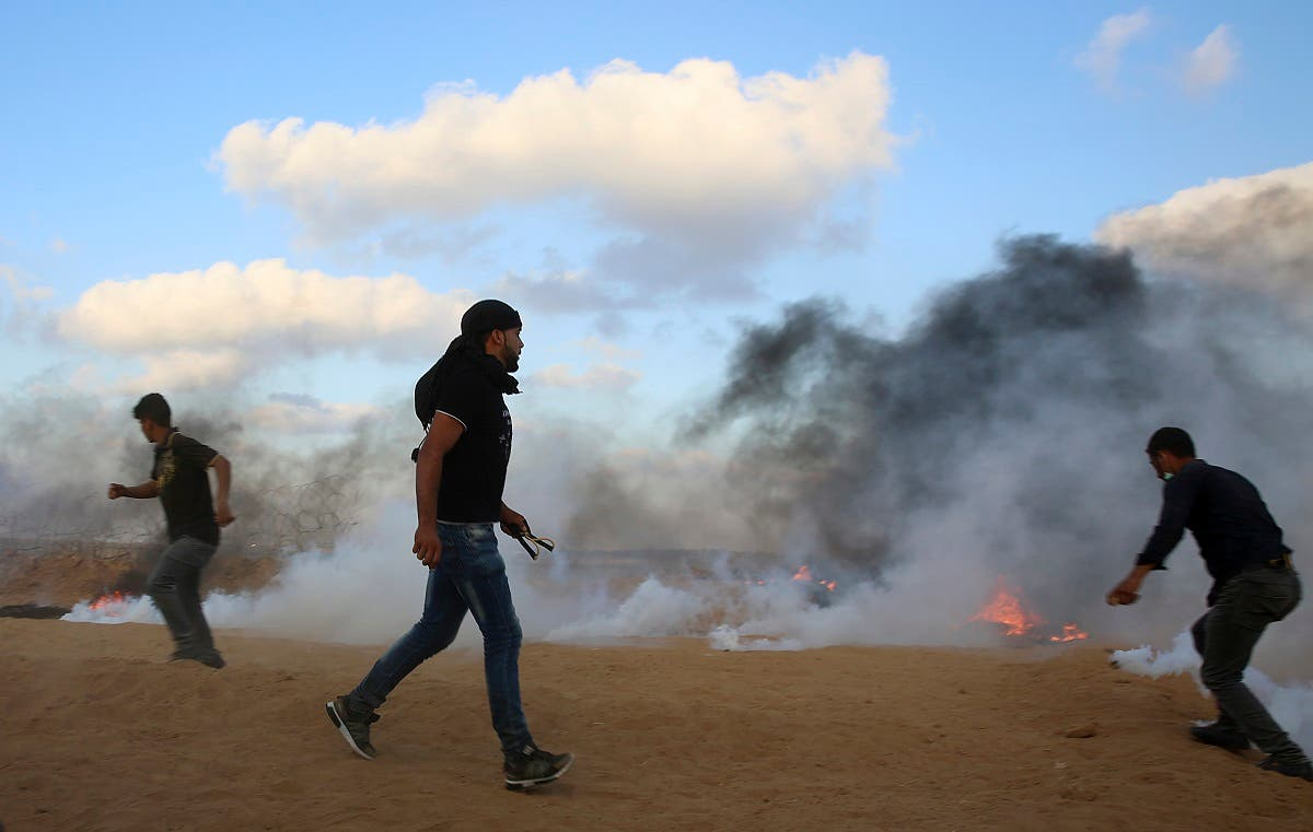 Protesters try to throw back teargas canisters fired by Israeli troops near the fence of the Gaza Strip border with Israel, during a protest east of Khan Younis, southern Gaza Strip, Friday, July 20, 2018. (AP)