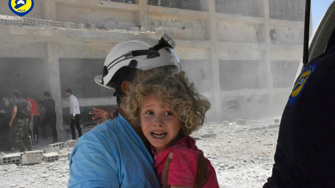 This photo provided by the Syrian Civil Defense group known as the White Helmets, shows a civil defense worker carrying a child after airstrikes hit a school housing a number of displaced people. (AP)